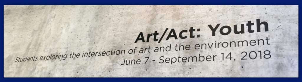 Sign on wall for Art/Act: Youth exhibit at David Brower Center