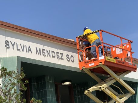 Photo of workers installing new signage for Sylvia Mendez School on Aug. 11 and 12, 2018.