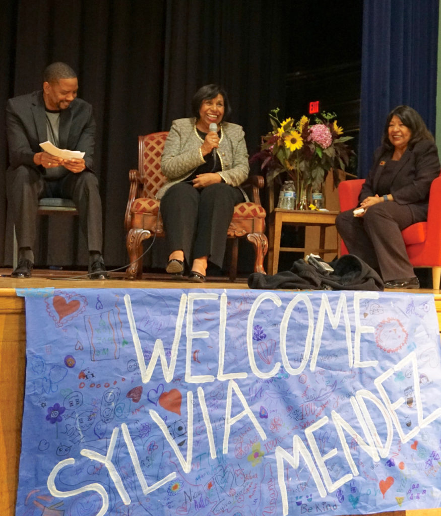 Photo of Sylvia Mendez on stage with Superintendent Donald Evens and her sister Sandra Mendez Duran at Mendez School, Sept. 14