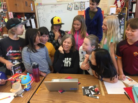 This is a photo of Maggie Riddle sitting at a table surrounded by elementary school students.