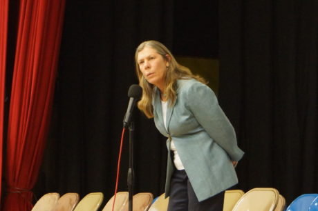 This is a photo of Maggie Riddle on stage and speaking into a microphone at a school assembly.