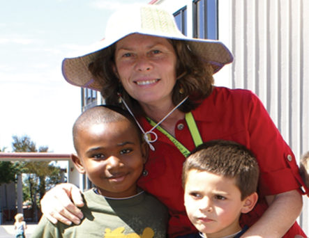 Maggie Riddle in a big hat outside with two young elementary school students.