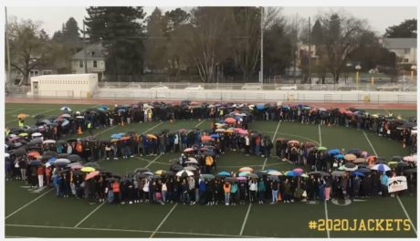This is a photo of Berkeley High School students standing in the rain on the football field forming the shape of a peace sign.