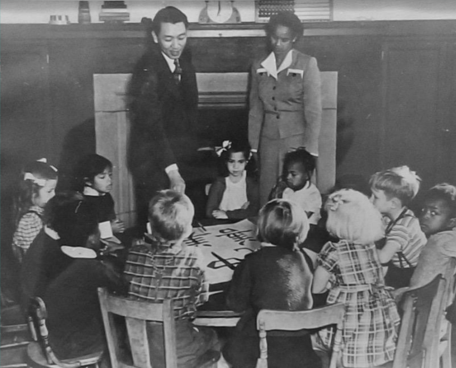 This is a photo of teacher Ruth Acty, with an unidentified man, standing in front of a table filled with elementary school children.