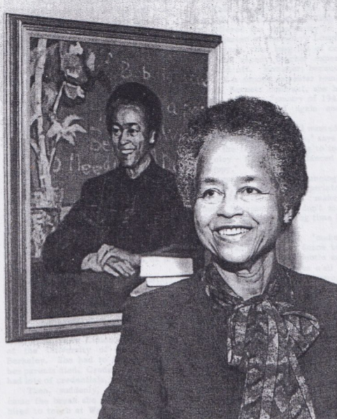 This is a photo of an older Ruth Acty, standing in fron of a painting of her image.